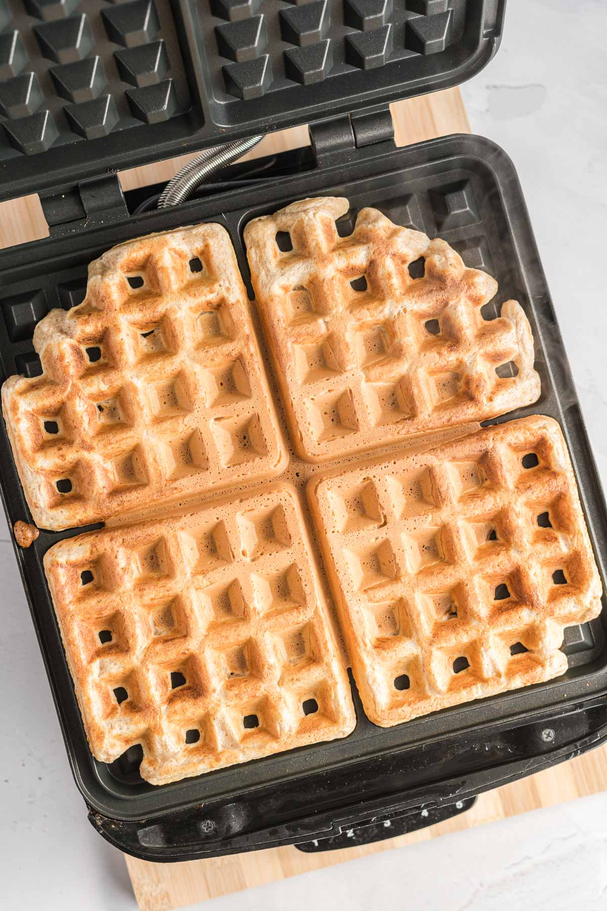 Four cooked waffles on a non-stick waffle iron.