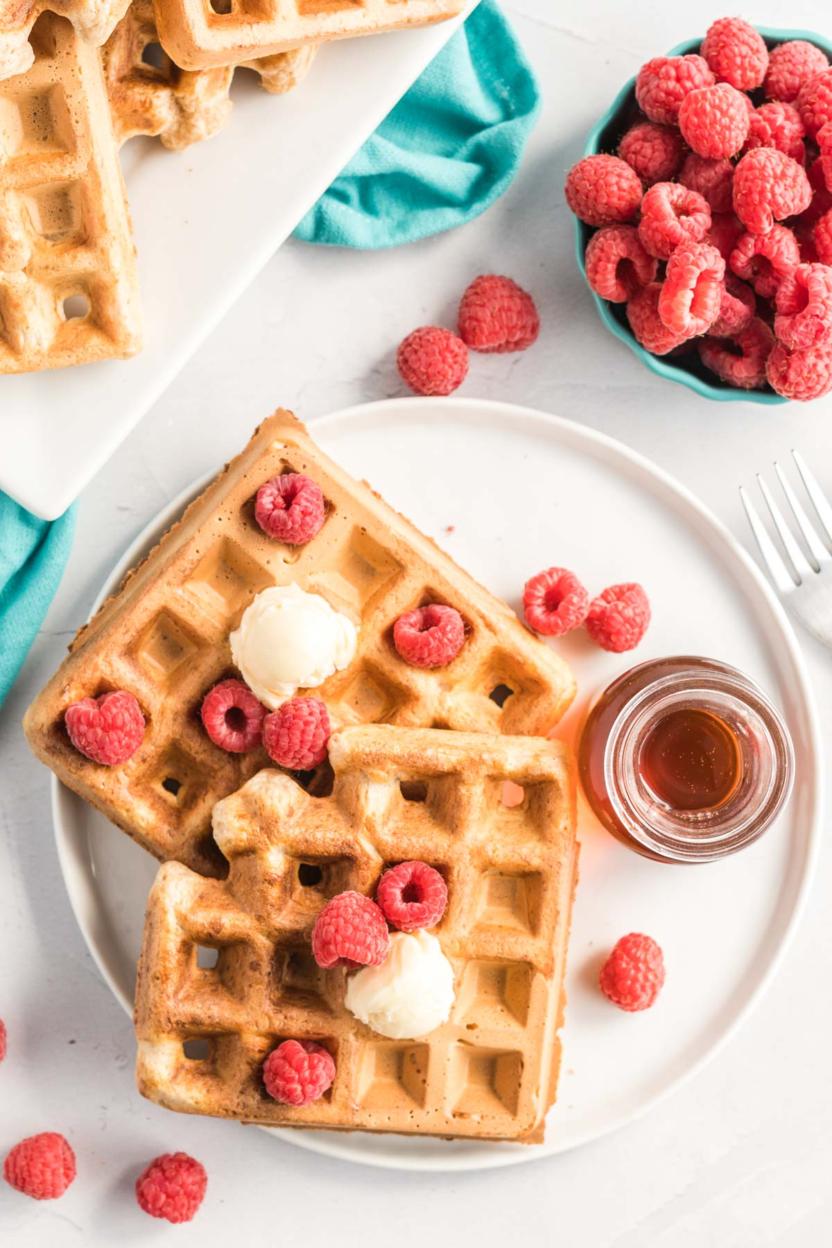 Two waffles on a plate with butter and raspberries and a small jar of syrup.