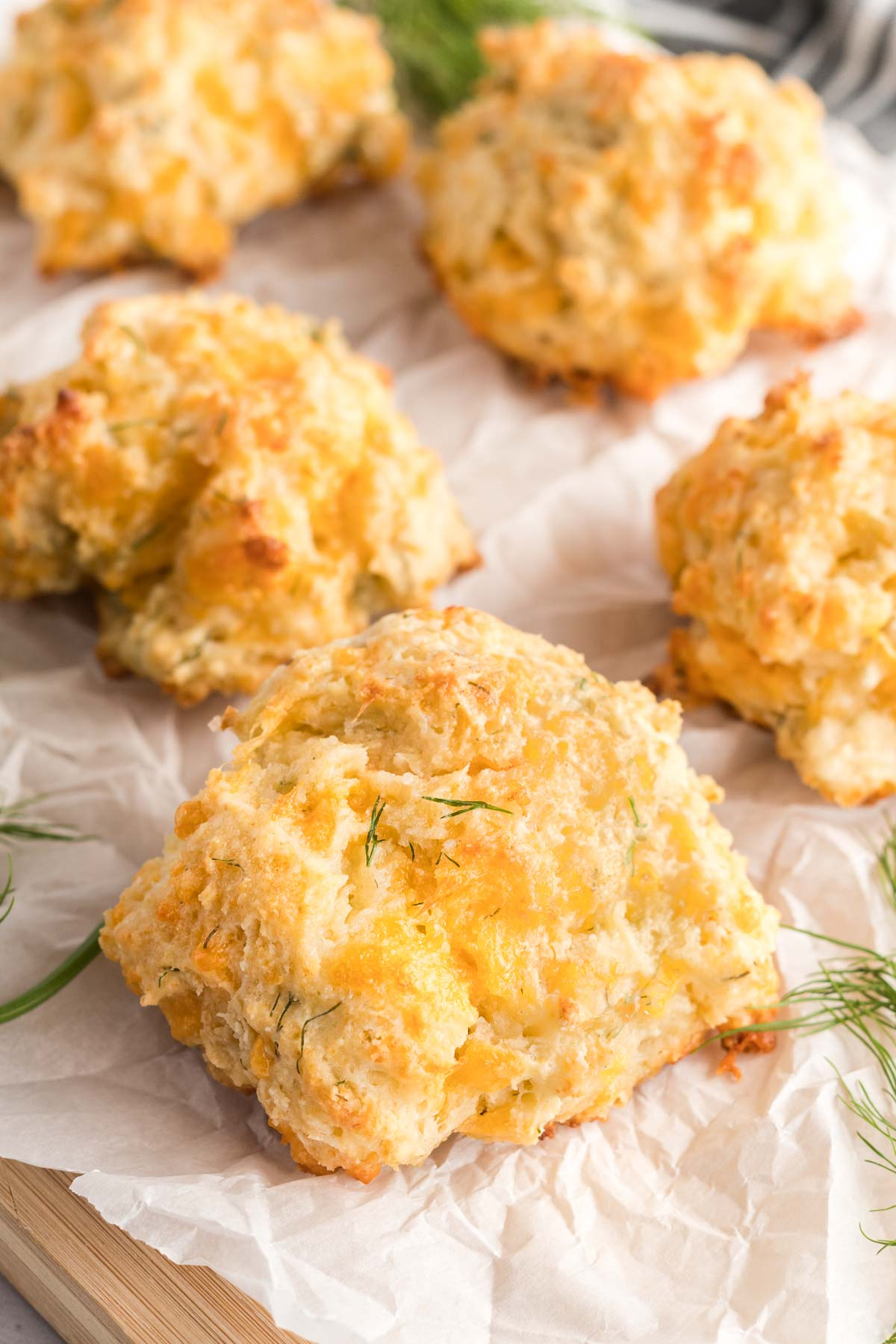 Biscuits in a single layer on parchment paper and garnished with fresh dill.