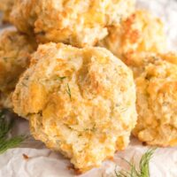 Cheddar biscuits in a small pile on parchment paper.