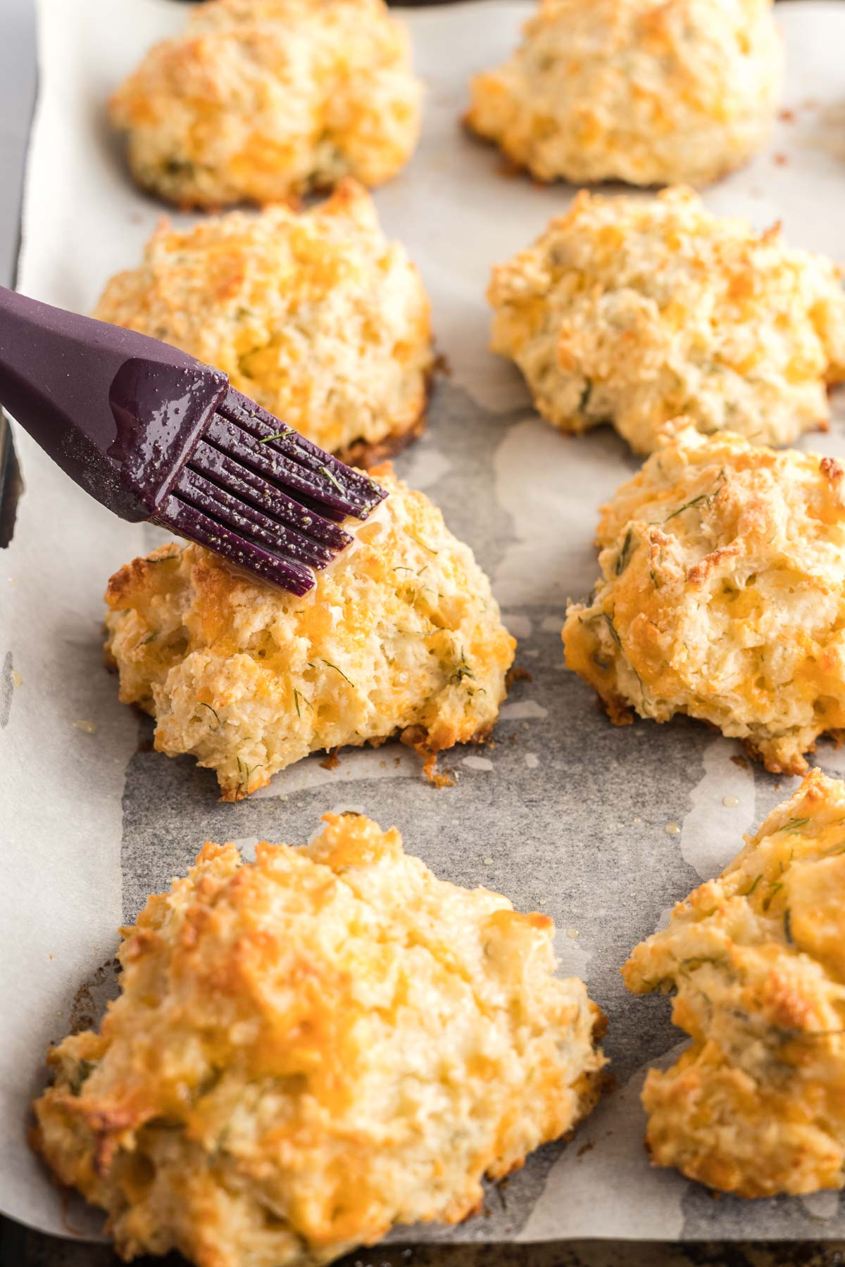 Baked biscuits on a baking sheet being brushed with melted butter using a silicone pastry brush.