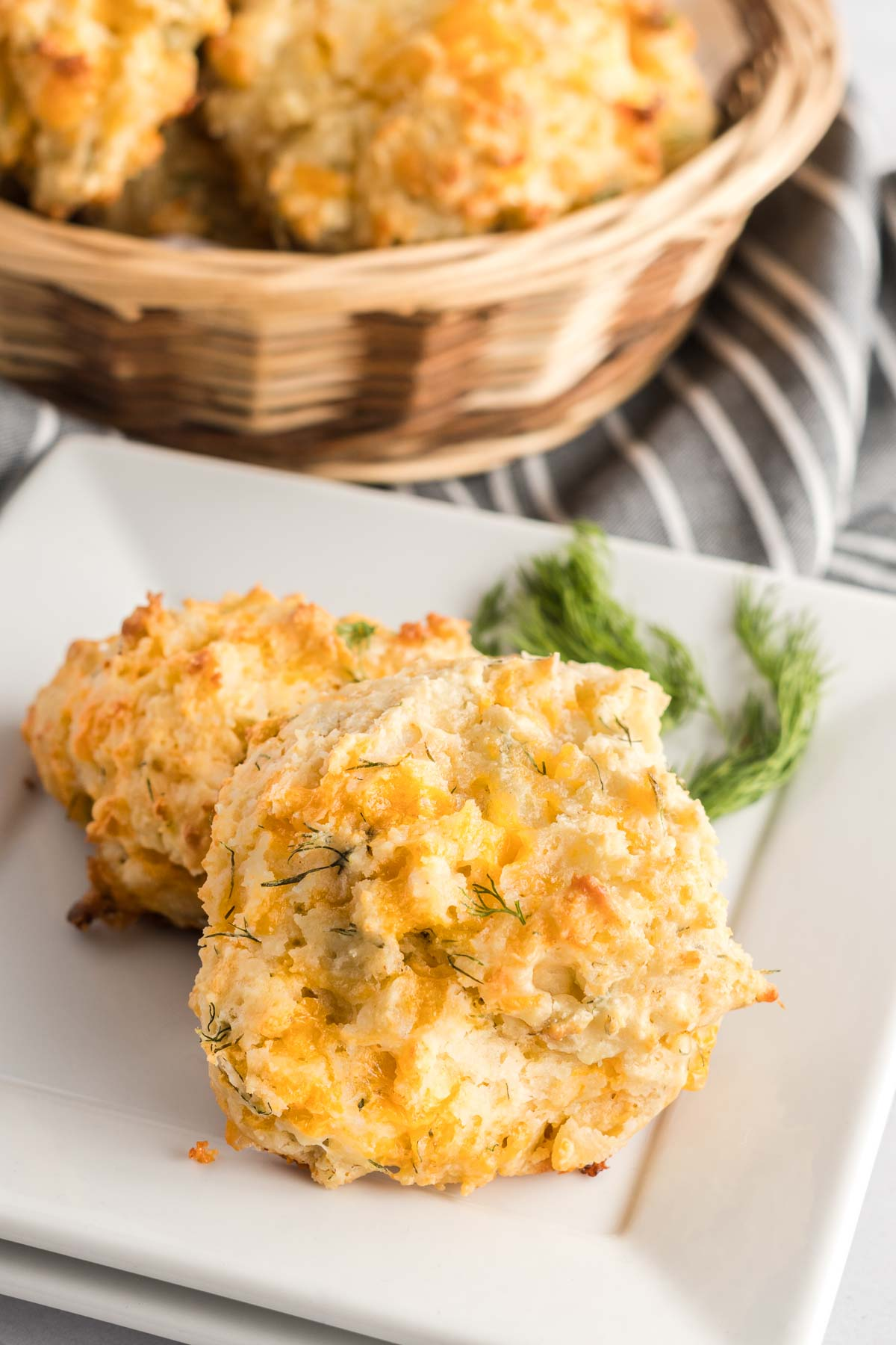 Two biscuits on a plate garnished with fresh dill and a basket of biscuits in the background.