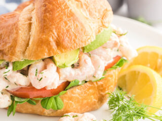 Shrimp on a croissant with pea shoots, tomato and avocado slices.
