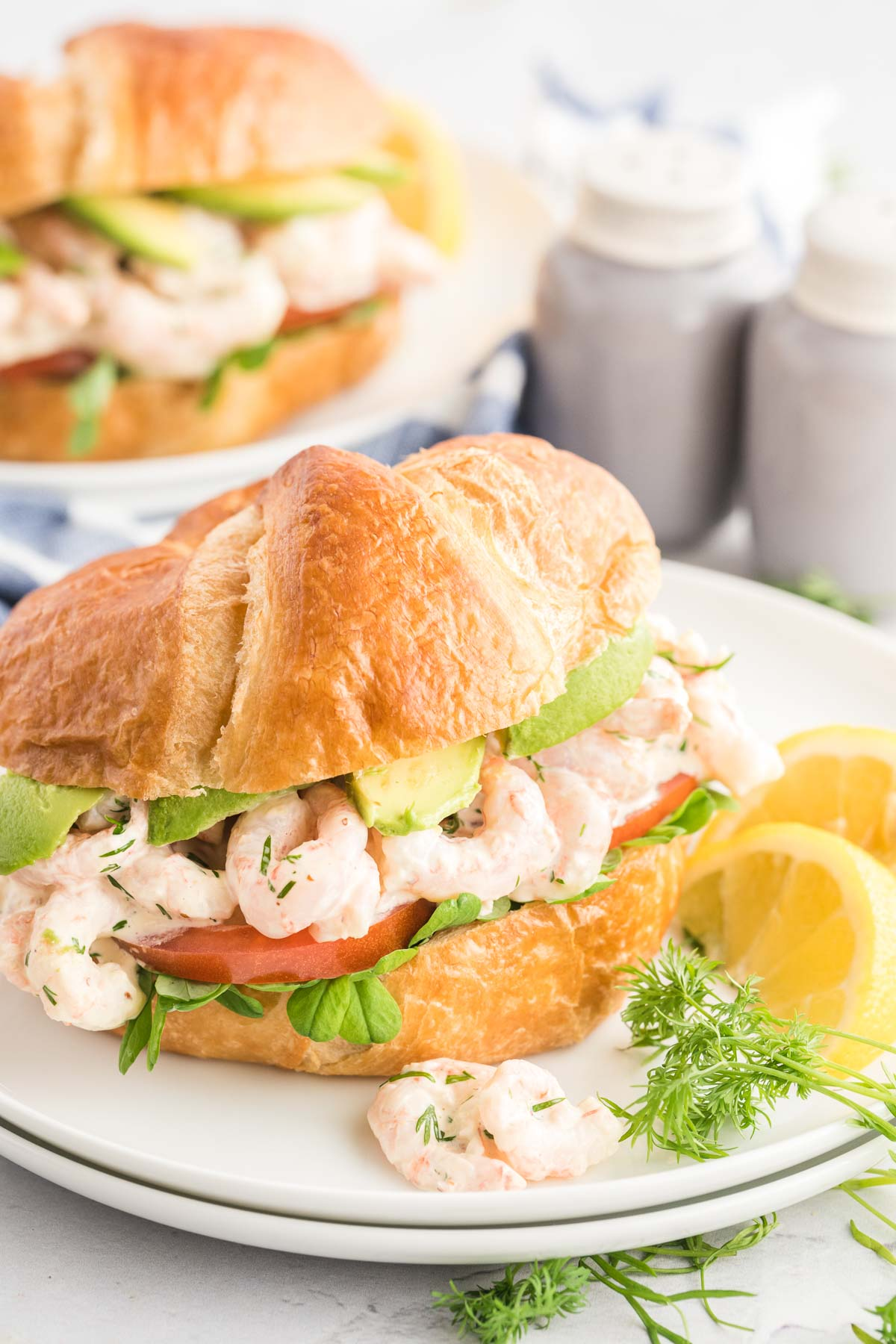 Two shrimp sandwiches on plates garnished with fresh dill and lemon slices.  Salt and pepper shakers in the background.