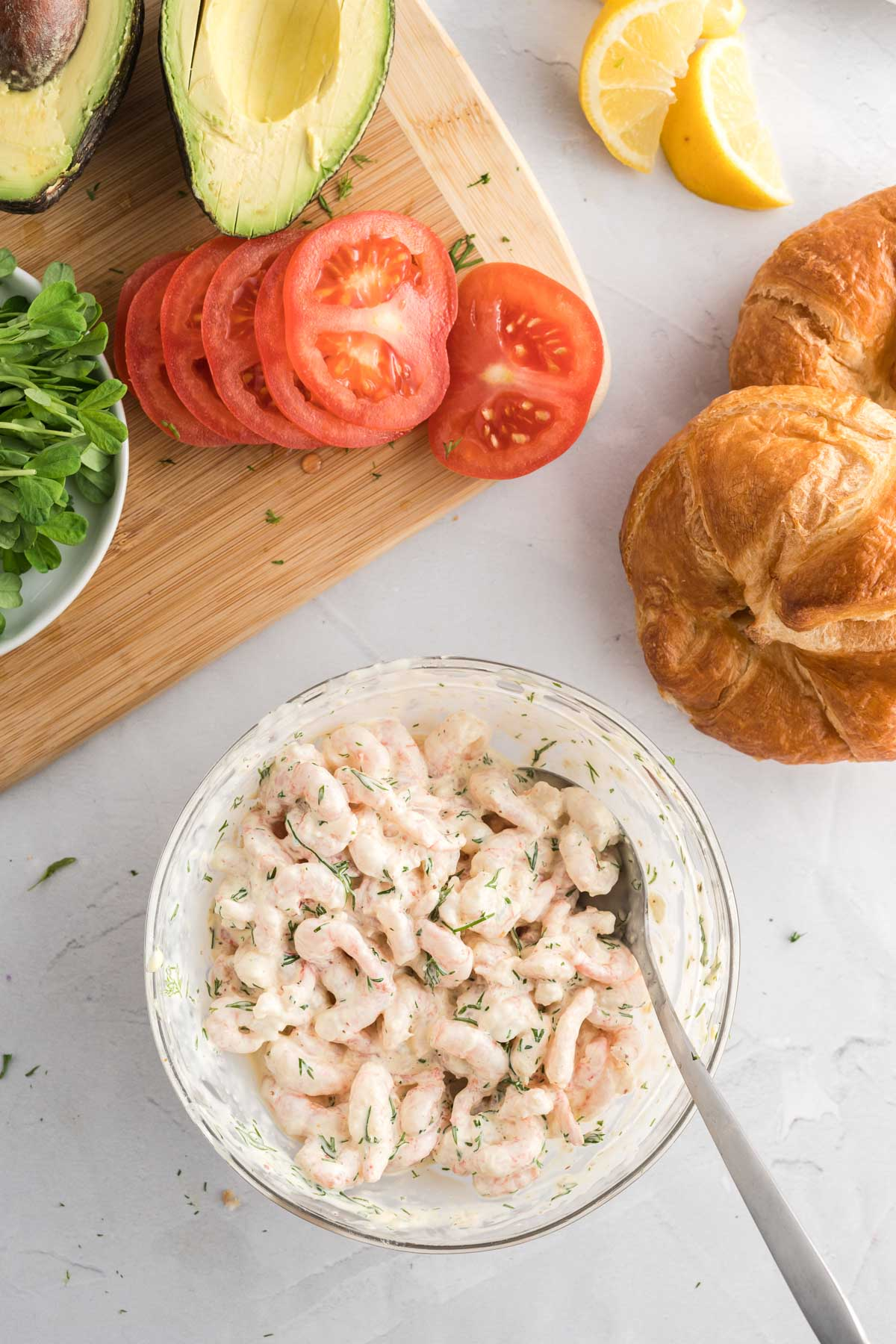Shrimp in a bowl mixed with mayonnaise, mustard, lemon juice and fresh dill.