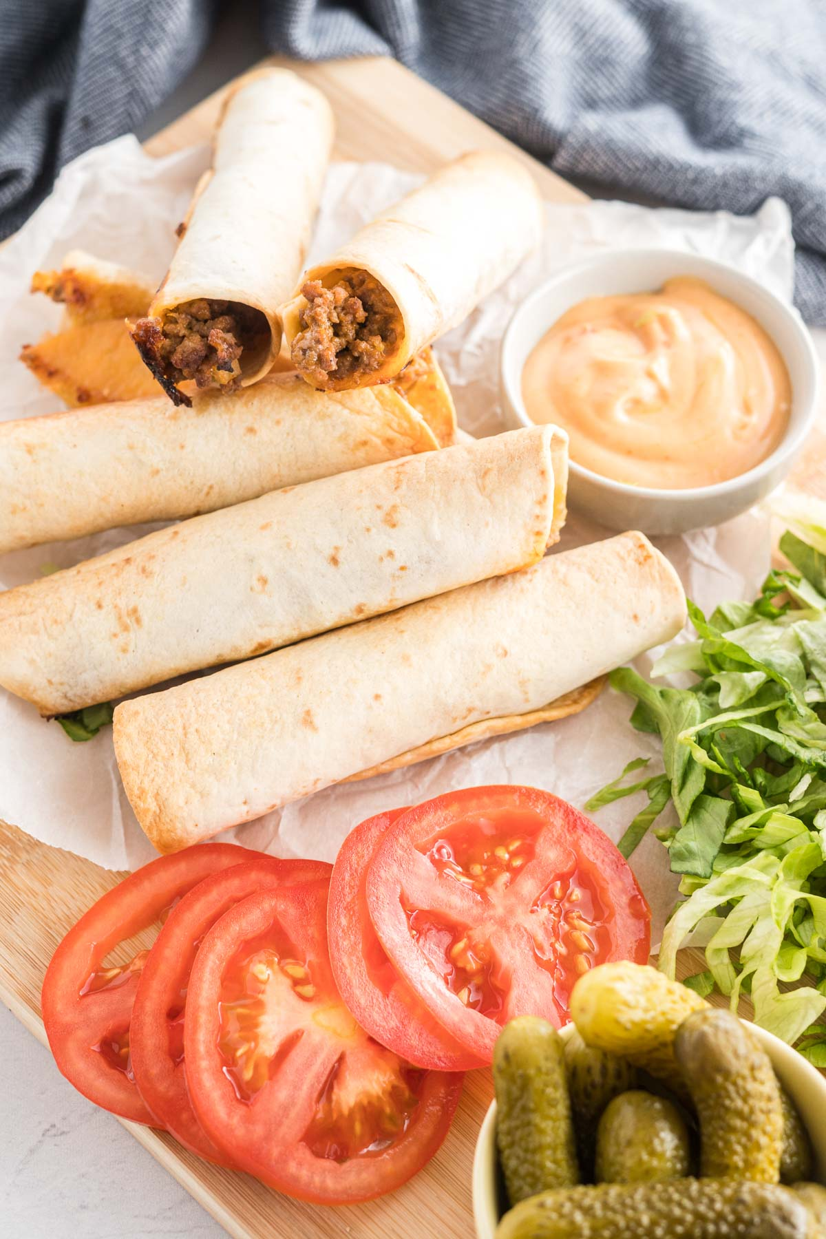 Taquitos on a platter with sliced tomatoes, shredded lettuce, dill pickles and a dish of burger sauce.