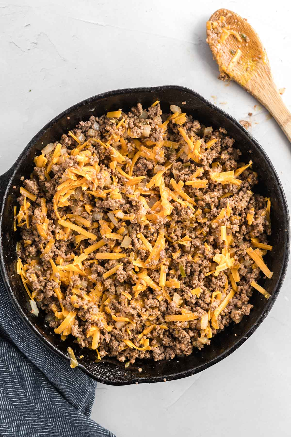Cooked ground beef in a cast iron skillet with cheese.