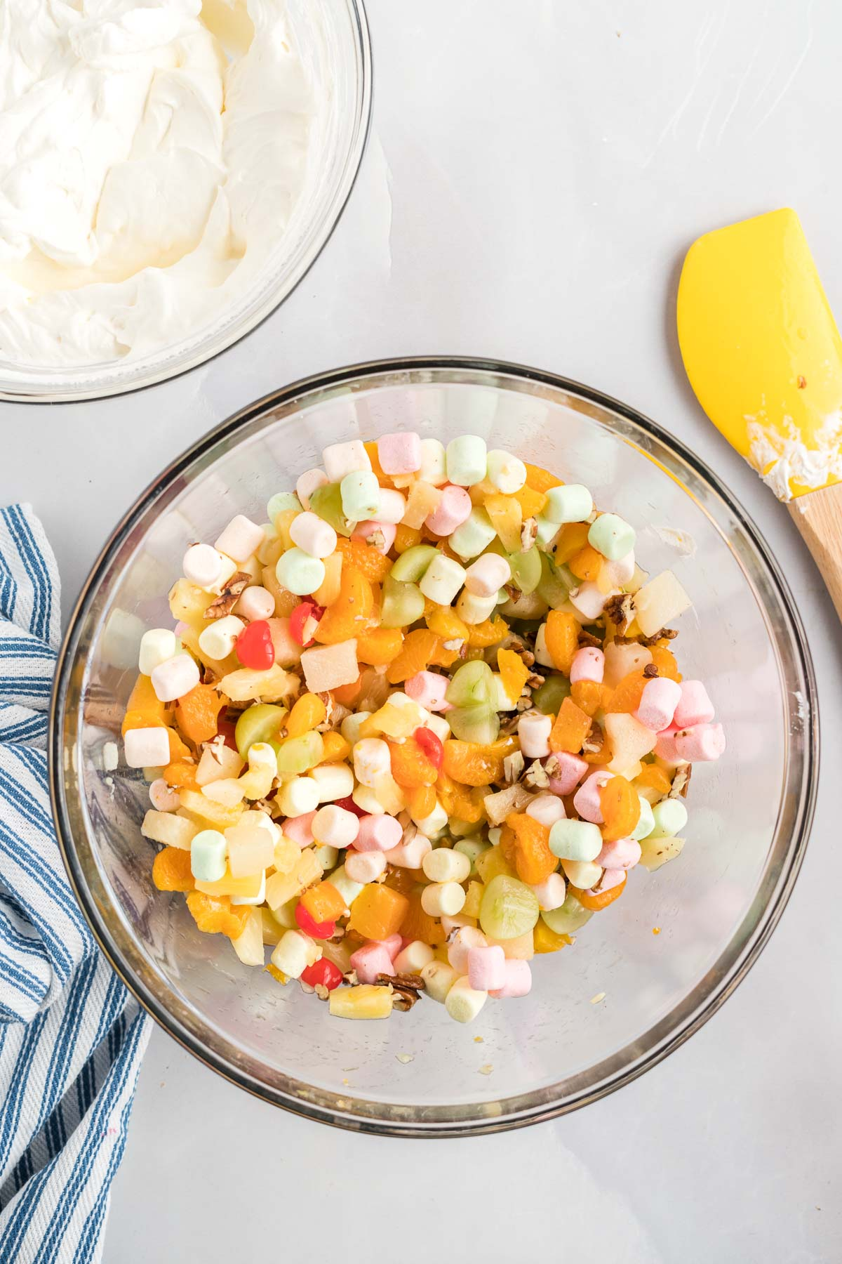 Fruit,marshmallows and nuts mixed in a large bowl.