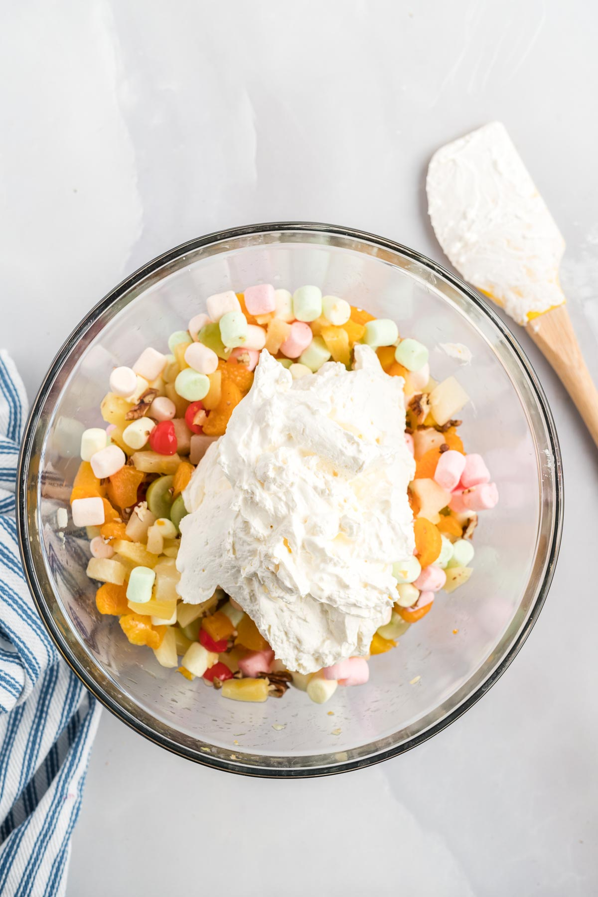 Cool whip added to a bowl of fruit, marshmallows and nuts.