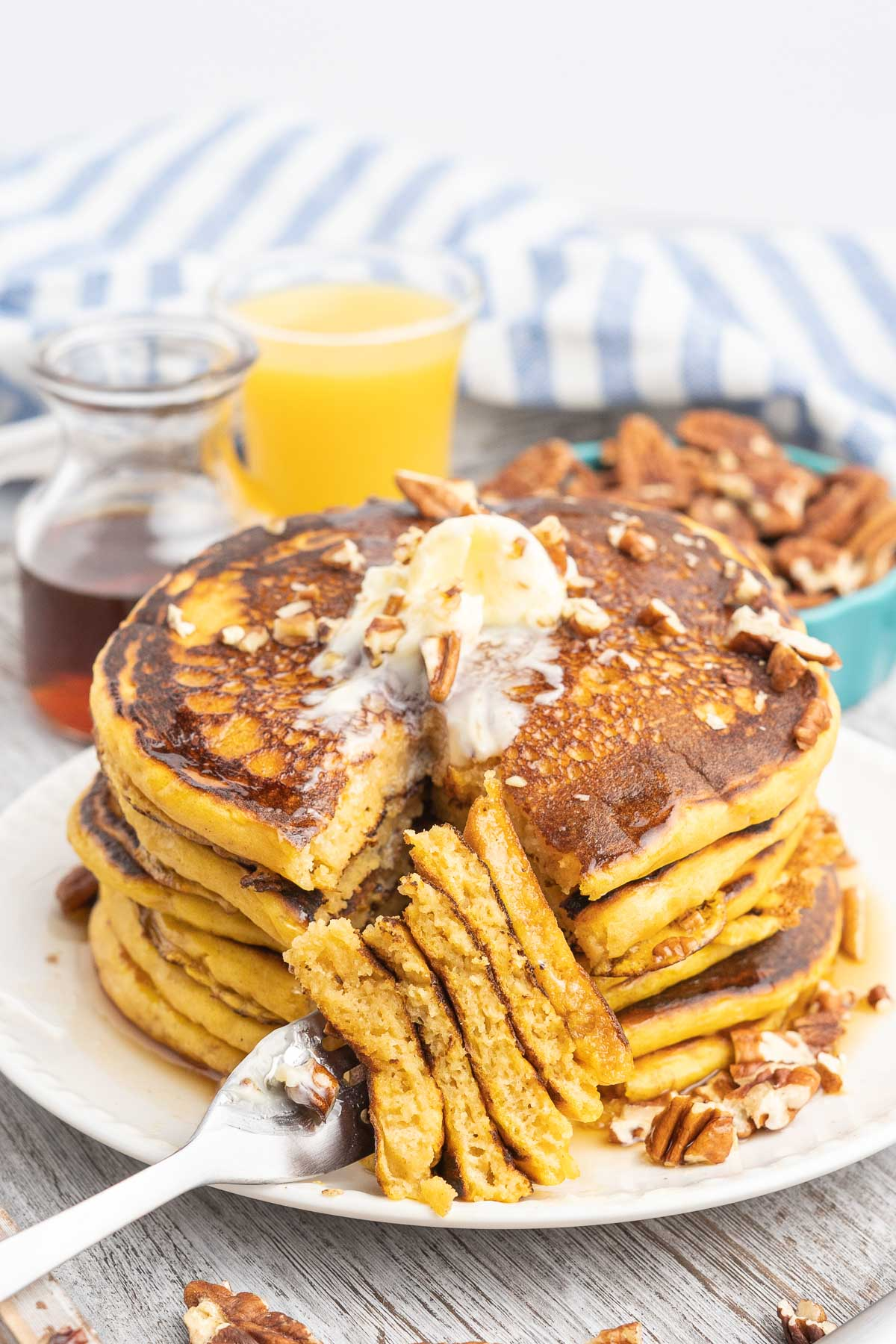 Pancakes served with a glass of orange juice and maple syrup and pecans on the side.