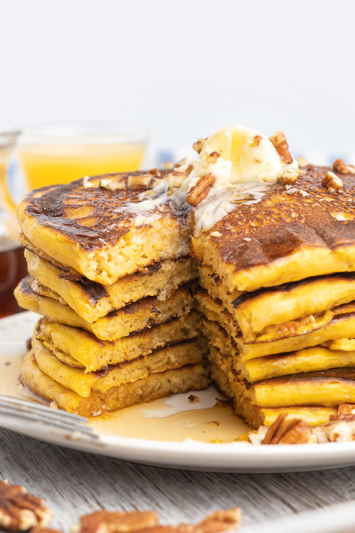 Stack of pancakes with wedge cut out topped with butter and syrup.