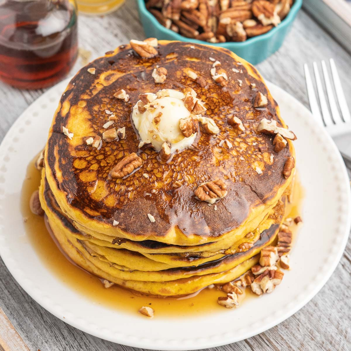 Pumpkin pancakes stacked on a plate topped with butter, syrup and chopped pecans.