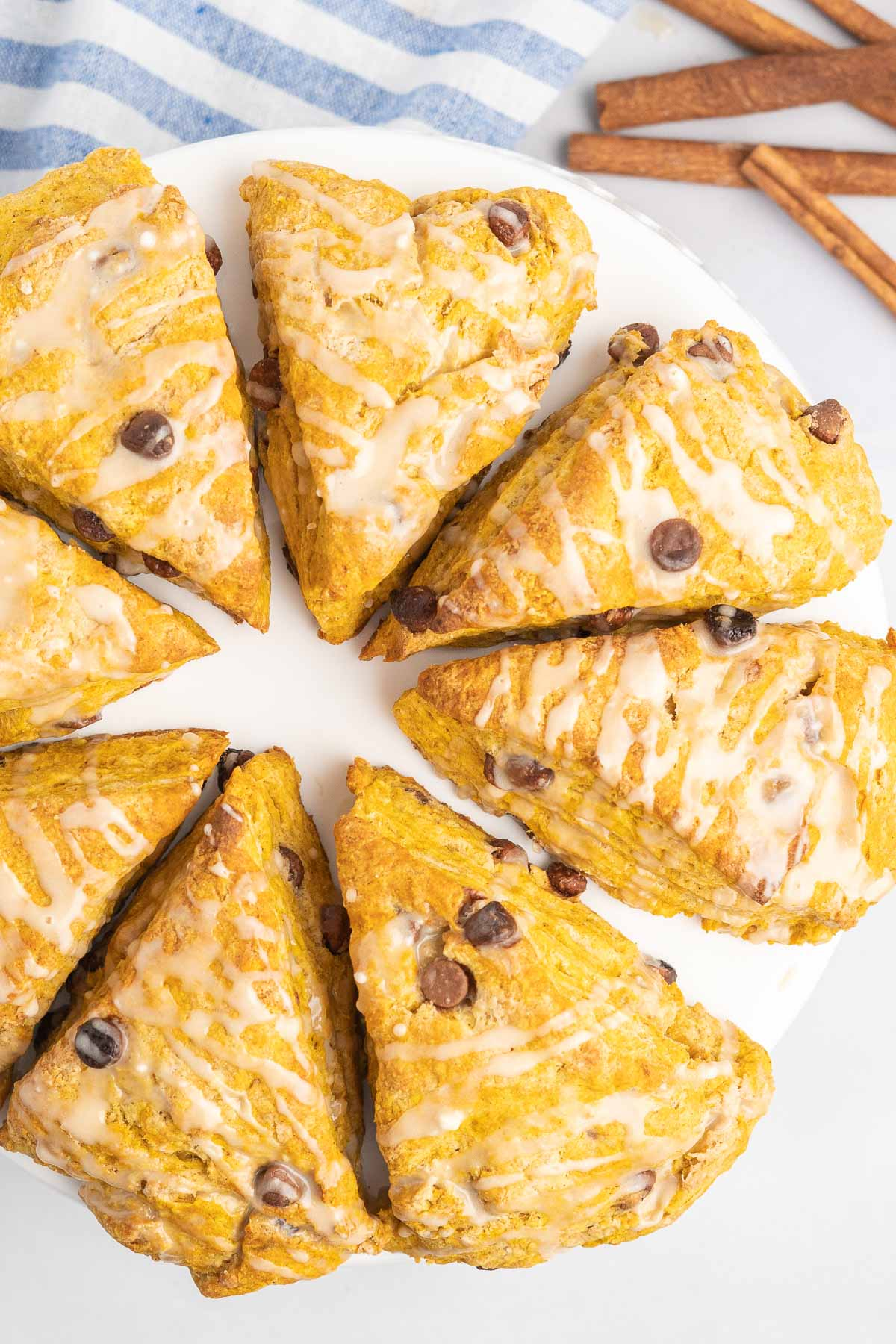 Pumpkin scones with icing drizzle on a serving plate.