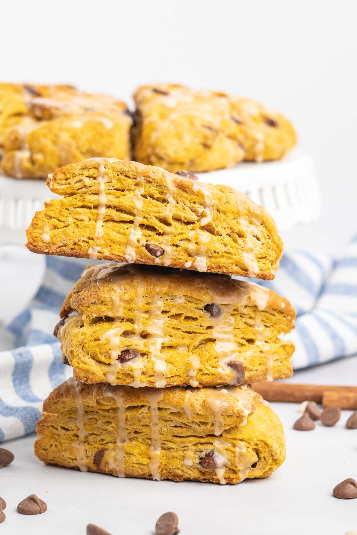 Three pumpkin scones in a stack with a plate of scones in the background.