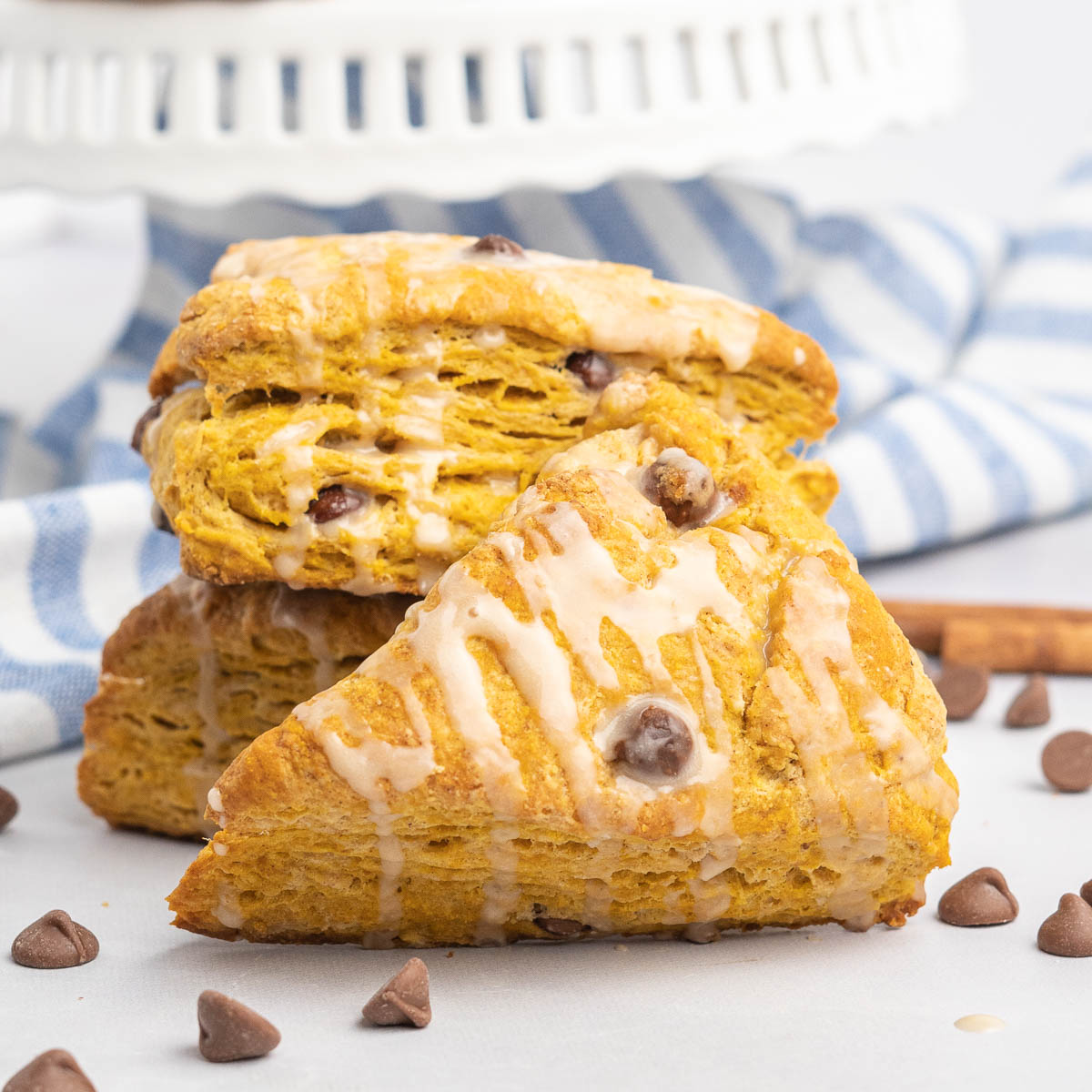 Three pumpkin scones with icing drizzle and chocolate chips.