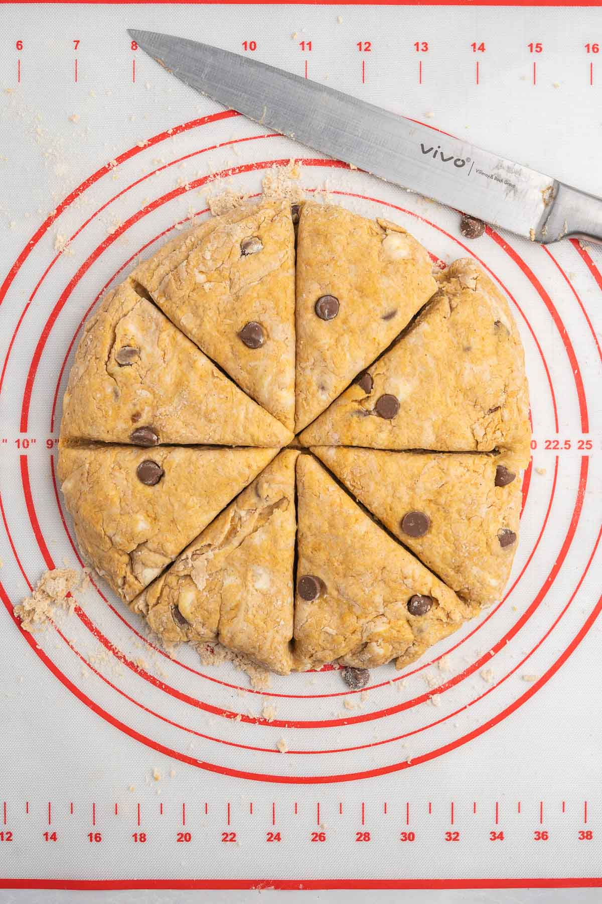 Scone dough pressed into a circle and cut into 8 wedges with a knife.