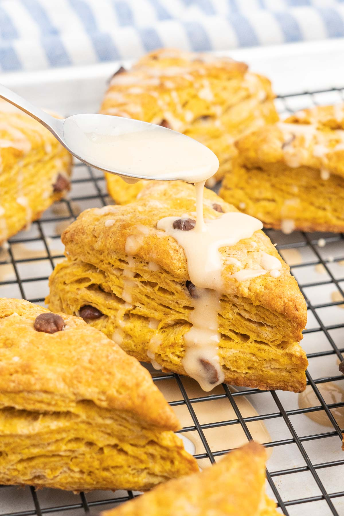 Pumpkin scone on a cooling rack being drizzled with icing.